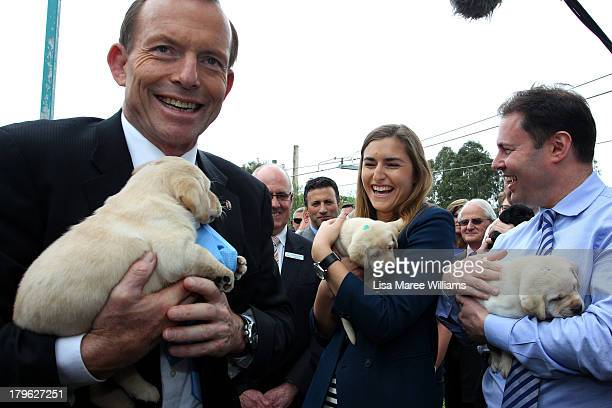 Australian Opposition Leader Tony Abbott his daughter Frances and Liberal MP Josh Frydenberg hold a puppy at Victoria Guide Dogs on September 6 2013...