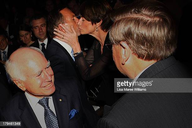 Australian Opposition Leader Tony Abbott is kissed by his wife Margie Abbott and congratulated by John Howard during a fundraiser dinner in Lilyfield...