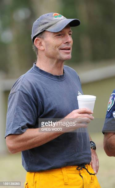 Australian opposition leader Tony Abbott listens to a bushfire briefing as he prepares to help in his capacity as a member of the rural fire service...