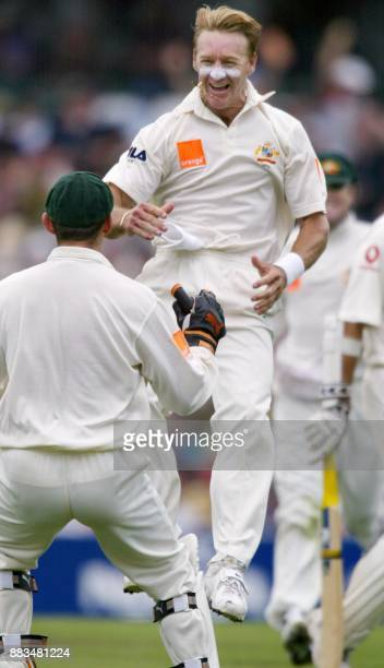 Australian paceman Andy Bichel celebrates having England opener Marcus Trescothick out with teammate Adam Gilchrist on the first morning of the fifth...
