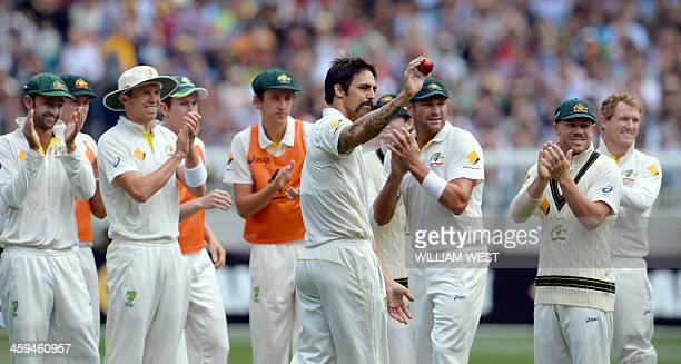 Australian paceman Mitchell Johnson gestures to the English fans after taking his fifth England wicket on the second day of the fourth Ashes cricket...