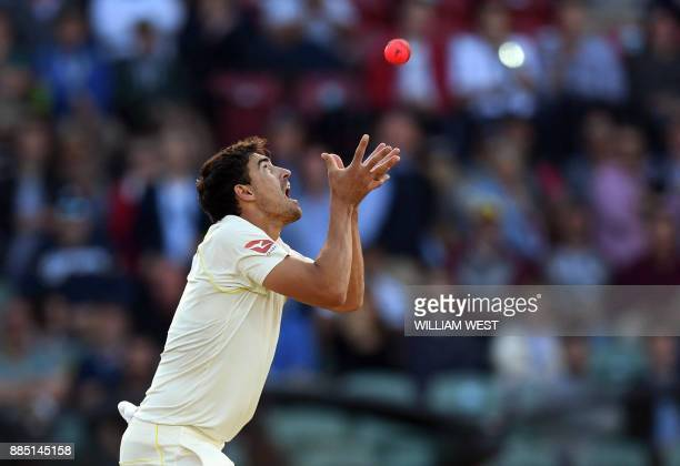 Australian paceman Mitchell Starc takes a catch to dismiss England batsman Chris Woakes on the third day of the second Ashes cricket Test match in...