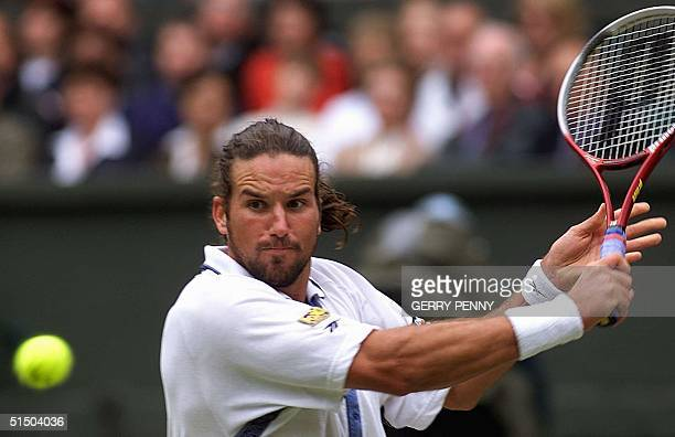 Australian Patrick Rafter eyes the ball before returning a backhand slice during his semifinal match in the Wimbledon championships against US Andre...