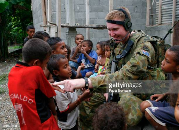 Australian peacekeeper Private Tim HuntSmith from New South Wales plays with East Timorese children while on patrol April 10 2007 in Dili East Timor...