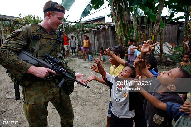 Australian peacekeeper Private Tim HuntSmith plays with East Timorese children while on patrol April 10 2007 in Dili East Timor East Timor's first...