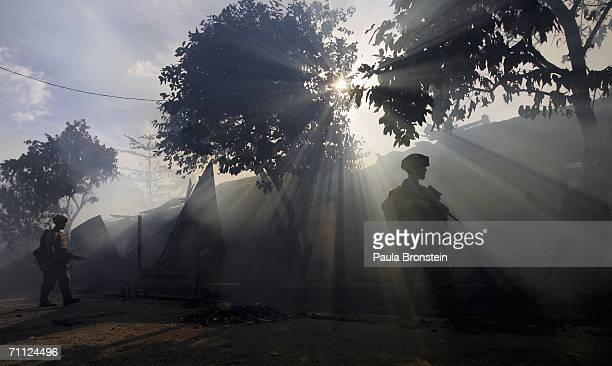 Australian peacekeeping soldiers patrol through the smoke from an entire block of burning homes on June 5 2006 in Dili East Timor Australia wants the...