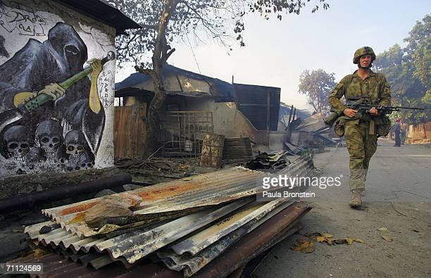Australian peacekeeping soldiers patrol through the smoke from an entire block of burning homes with Graffiti on a walls depicting death June 5 2006...