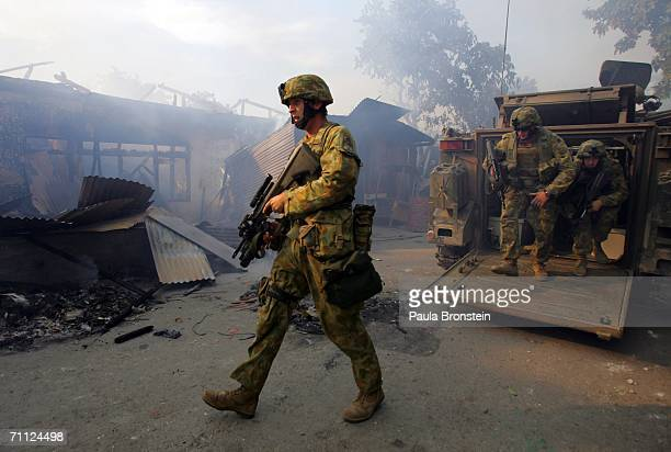 Australian peacekeeping soldiers walk through the smoke from an entire block of burning homes on June 5 2006 in Dili East Timor Australia wants the...