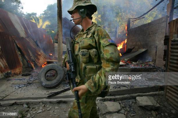 Australian peacekeeping soldiers walks by a fire at a house torched by alleged gang violence June 7 2006 in Dili East Timor Australia is asking...