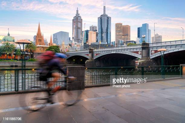 australian people cycling  for exercise near yarra river with view of the melbourne city financial district with skyscrapers in morning at melbourne, victoria, australia. - melbourne austrália - fotografias e filmes do acervo