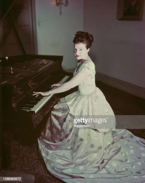 Australian pianist Eileen Joyce wearing a 'New Look' dress plays a grand piano in England in February 1948