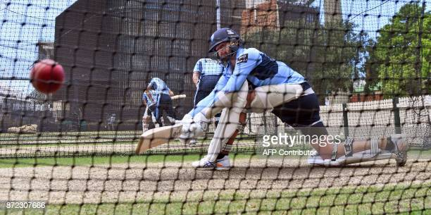 TOPSHOT Australian player Nathan Lyon sweeps a ball during training with the New South Wales state cricket team in Sydney on November 10 2017...