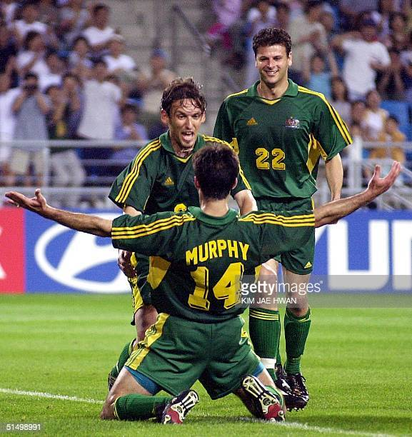 Australian player Shaun Murphy celebrates after scoring a goal with teammates Mile Sterjovski and Tony Popovic during their FIFA's Confederations Cup...
