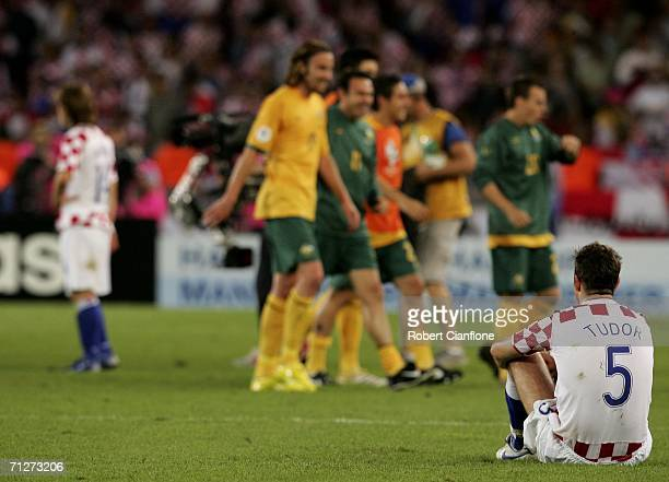 Australian players celebrate as a dejected Igor Tudor of Croatia sits on the pitch following his team's 22 draw and exit from the competition during...