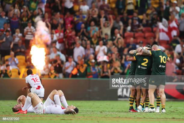 Australian players celebrate victory as England players lay dejected during the 2017 Rugby League World Cup Final between the Australian Kangaroos...