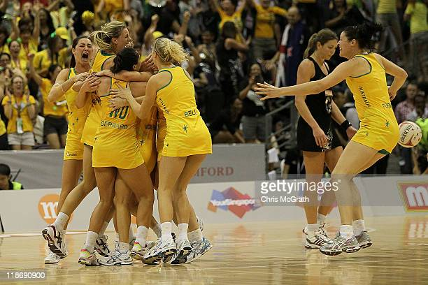 Australian players celebrate victory as Irene van Dyk of New Zealand walks from the court during the final match between Australia and New Zealand on...