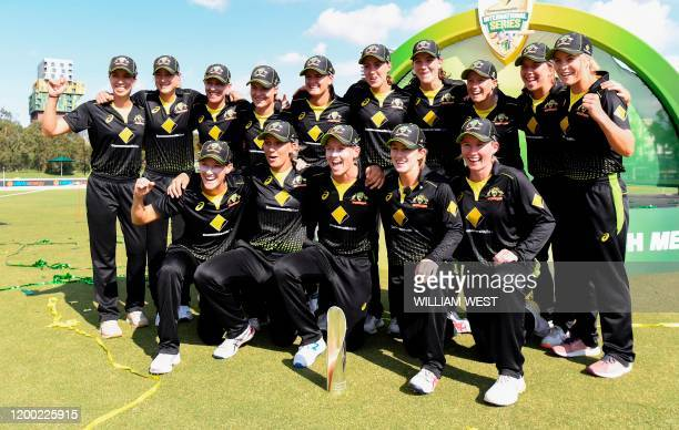 Australian players celebrate with the trophy after defeating India in the final of their women's T20 international triseries cricket match in...