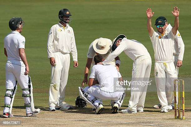 Australian players help Ryan McLaren of South Africa after he was hit by a delivery from Mitchell Johnson of Australia during day four of the First...