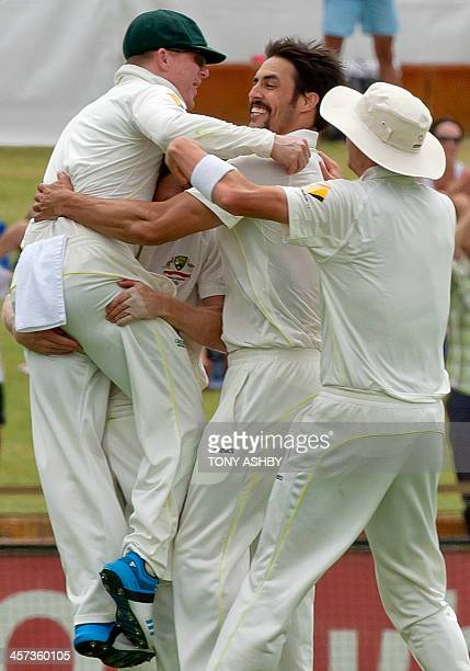 Australian players jump on Mitchell Johnson as they celebrate taking the wicket of England batsman Tim Bresnan on the fifth day of the third Ashes...