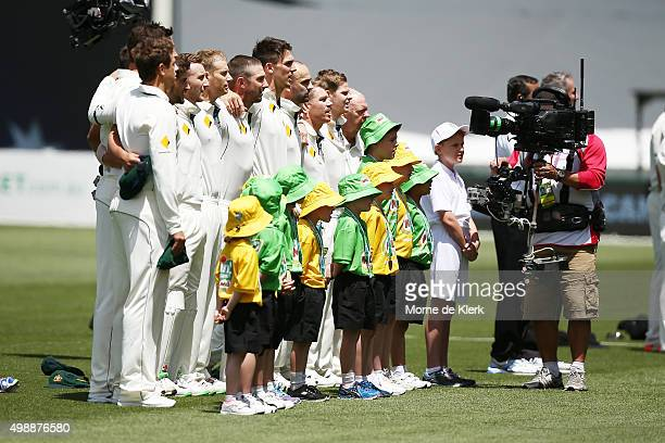 Australian players sing the anthem before play on day one of the Third Test match between Australia and New Zealand at Adelaide Oval on November 27...