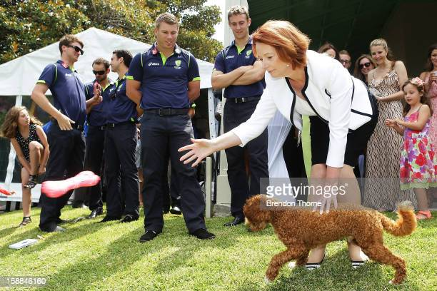 Australian players watch Australian Prime Minister Julia Gillard throw a soft toy for her dog 'Reuben' during a function at Kirribilli House on...