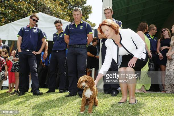 Australian players watch Australian Prime Minister Julia Gillard pat her dog 'Reuben' during a function at Kirribilli House on January 1 2013 in...