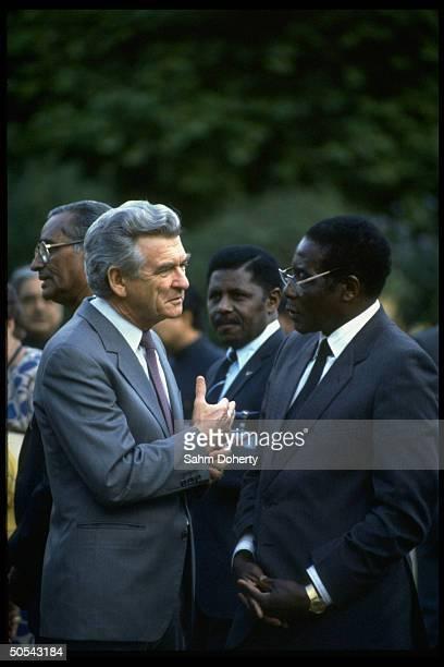 Australian PM Robert Hawke chatting w Zimbabwe ldr Robert Mugabe outside Commonwealth meeting