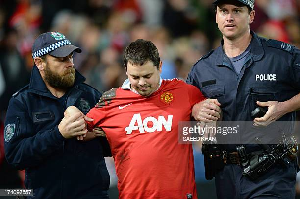 Australian police officers escort a fan from a tour match between Manchester United Foxtel ALeague Allstars in Sydney on July 20 2013 IMAGE STRICTLY...