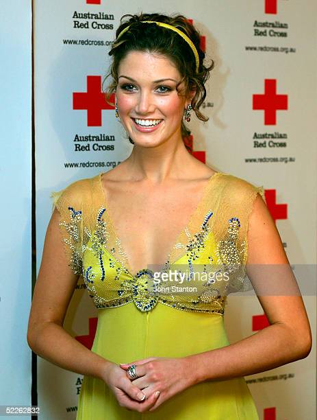 Australian pop star Delta Goodrem poses for photos as she arrives at the 90th anniversary gala dinner for the Australian Red Cross on March 2 2005 in...