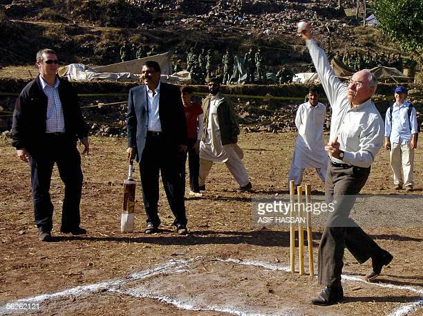 Australian Prime Minister John Howard delivers a ball as Pakistani Religious Minister Ejaz-ul-Haq holds a bat as they play cricket during their visit...