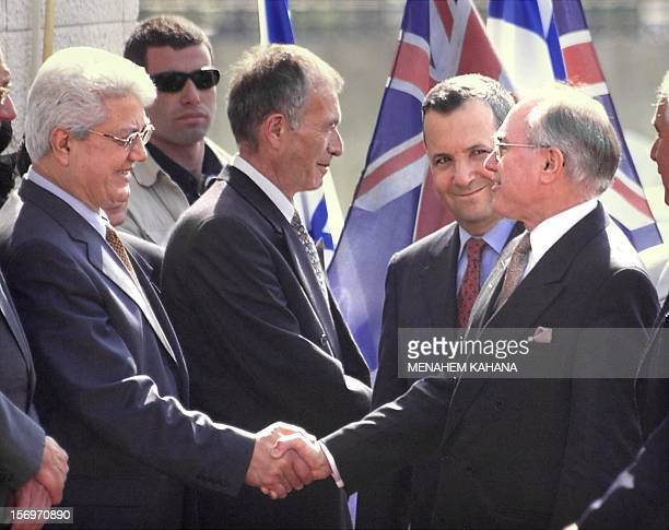 Australian Prime Minister John Howard escorted by his Israeli counterpart Ehud Barak shakes hands with Israeli Foreign Minister David Levy during a...