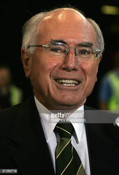 Australian Prime Minister John Howard puts on a brave face at Sydney International Airport 01 September 2004 as he waits for the Australian Olympic...