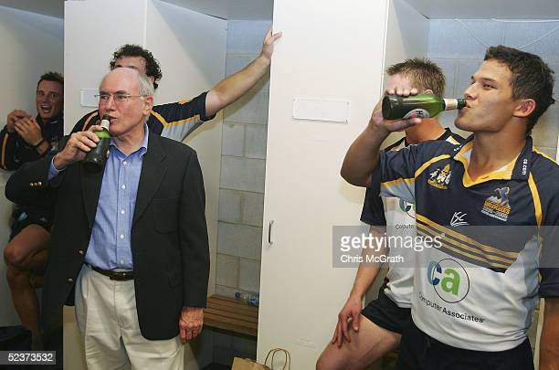 Australian Prime Minister John Howard shares a beer with Henari Veratau of the Brumbies after the Tooheys New Super 12 match between the Brumbies and...