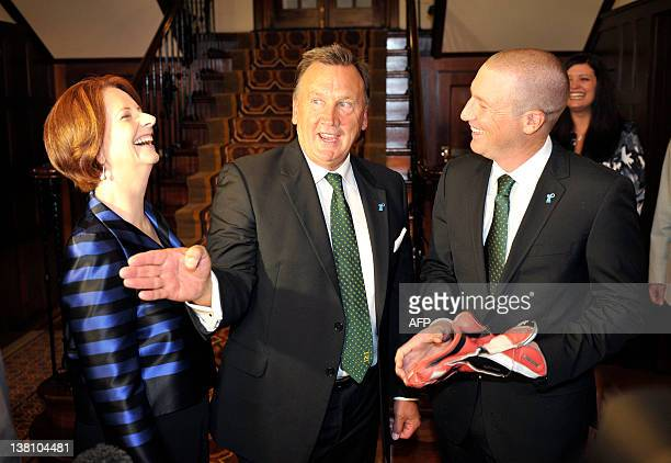Australian Prime Minister Julia Gillard and partner Tim Mathieson share a light moment over the batting glove presented to him by XI cricket captain...