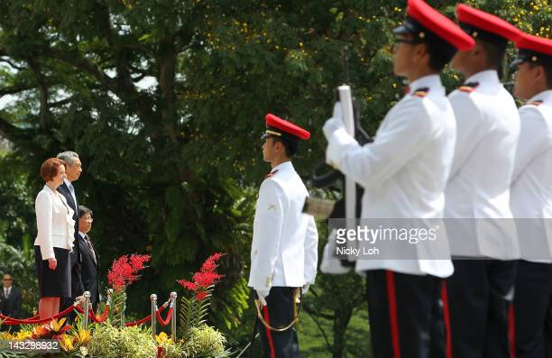 Australian Prime Minister Julia Gillard and Singapore Prime Minister Lee Hsien Loong attend a honour guard welcome ceremony at the Istana on April 23...