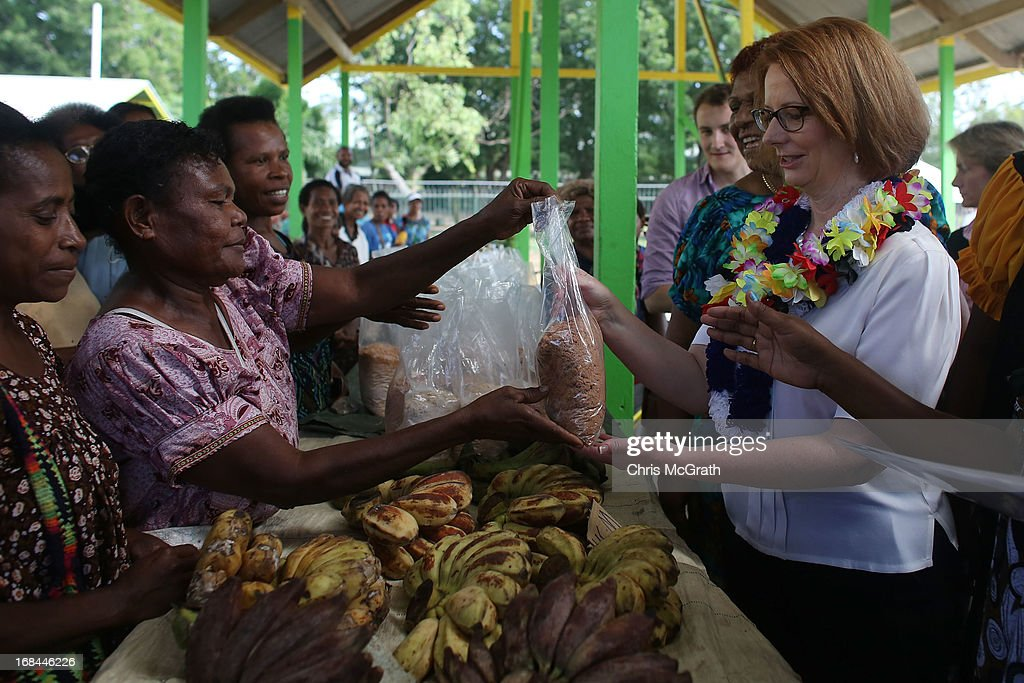 Australian Prime Minister Julia Gillard buys fruit and vegetables from a market seller during a tour of the Gerehu Market on May 10, 2013 in Port Moresby, Papua New Guinea. The three-day visit is a chance for the two nations to strengthen economic ties, with talks being held on key issues including, trade, military defense, and the controversial Australian detention center on Manus Island. The trip is the first official visit for Prime Minister Julia Gillard to the Pacific Island Nation and the first visit since former prime minster Kevin Rudd visited in 2007.