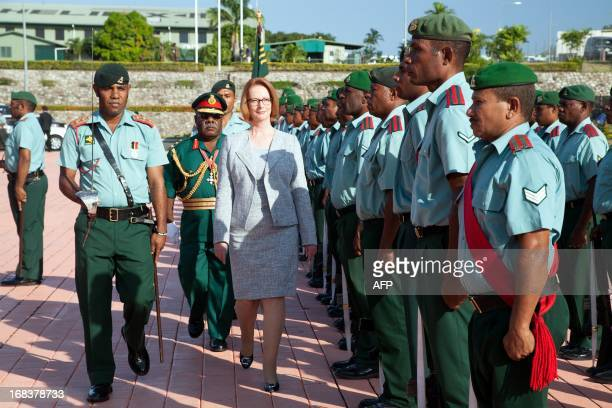 Australian Prime Minister Julia Gillard inspects a guard of honour upon arrival in Port Moresby Papua New Guinea on May 9 2013 Gillard is touring...