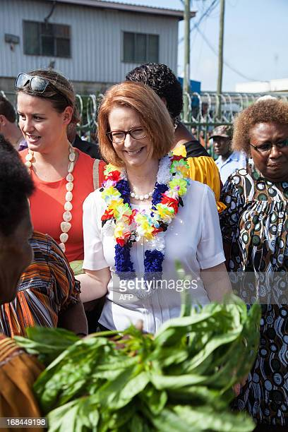 Australian Prime Minister Julia Gillard is greeted by market sellers in Gerehu market in Port Moresby during her trip to Papua New Guinea on May 10...