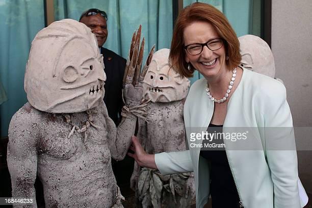 Australian Prime Minister Julia Gillard jokes around with members of the Goroka Asaro Mud Men dancers after meeting with Papua New Guinea Prime...