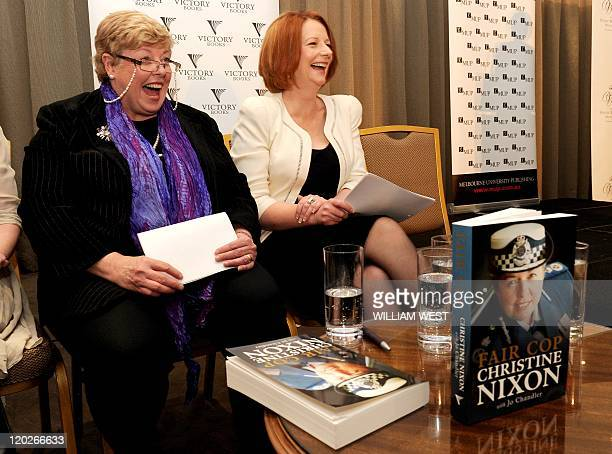 Australian Prime Minister Julia Gillard laughs as she launches the book 'Fair Cop' by former Victoria state police commissioner Christine Nixon in...