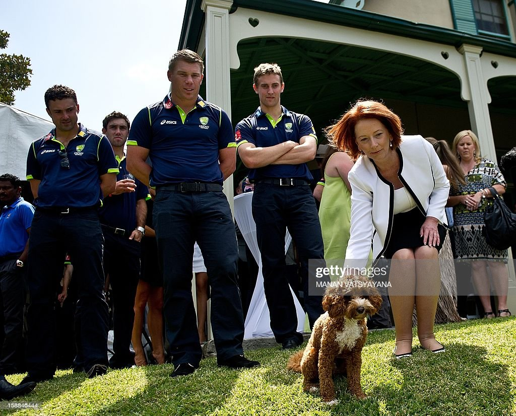 Australian Prime Minister Julia Gillard (R) pats her pet dog as cricketer David warner (2L) looks on during an afternoon tea at Kirribilli House in Sydney on January 1, 2013. Australia plays Sri Lanka in the third cricket Test starting at the Sydney Cricket Ground (SCG) on January 3.