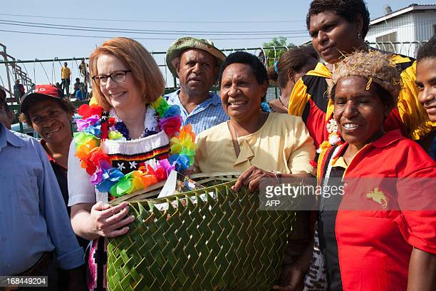 Australian Prime Minister Julia Gillard receives gifts from market sellers in Gerehu market in Port Moresby during her trip to Papua New Guinea on...