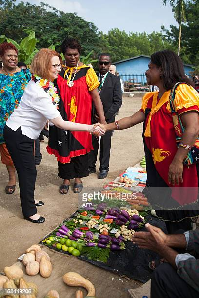 Australian Prime Minister Julia Gillard shakes hands with a market seller in Gerehu market in Port Moresby during her trip to Papua New Guinea on May...