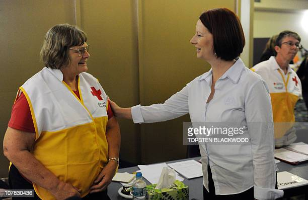 Australian Prime Minister Julia Gillard talks with an Australian Red Cross volunteer at an evacuation centre in Bundaberg on December 31 2010 Floods...