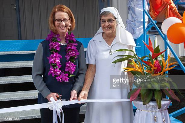 Australian Prime Minister Julia Gillard talks with the principal of Marianville school in Port Moresby during her trip to Papua New Guinea on May 10...