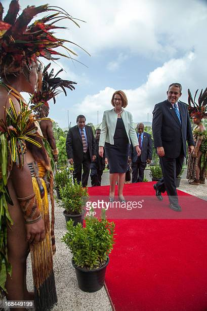 Australian Prime Minister Julia Gillard walks with MP Justin Tkatchenko past traditional dancers from Chimbu Province in Port Moresby during her trip...