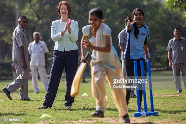 Australian Prime Minister Julia Gillard watches as children play cricket at a cricket clinic hosted by NGO Magic Bus NGO which helps underprivileged...