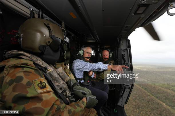 Australian Prime Minister Malcolm Turnbull points to the damage caused by Cyclone Debbie as he examines an area of Bowen in northern Queensland by...