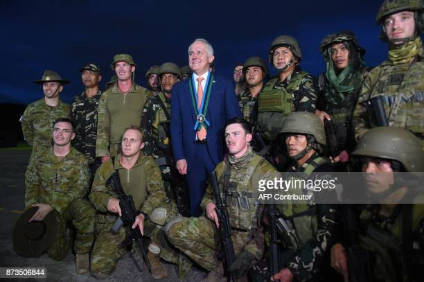 Australian Prime Minister Malcolm Turnbull poses in a group photo with soldiers after watching an antiterrorism simulation drill by Australian and...