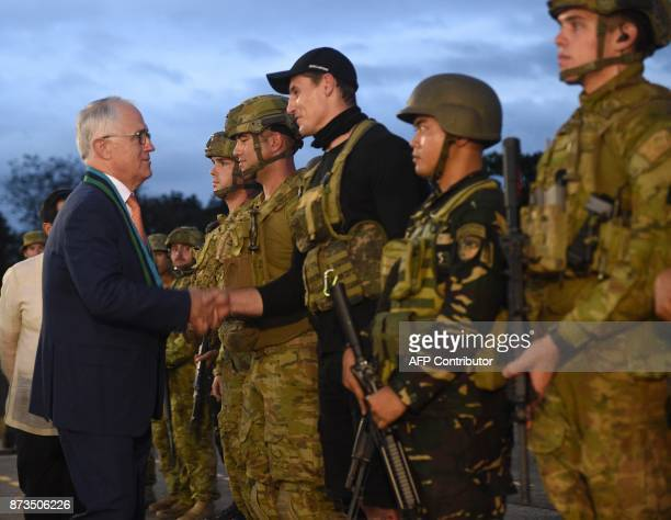 Australian Prime Minister Malcolm Turnbull shake hands with an Australian soldier after an antiterrorism simulation drill at the military...